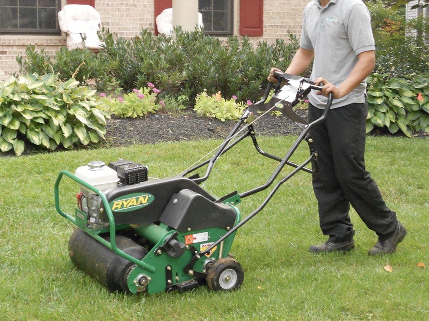 Man with gray shirt and black pants using the lawn mower